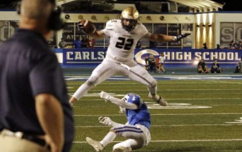 Cox hurdles a Carlsbad defender on his way to a first down.