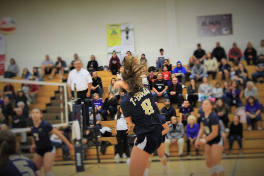 Senior Reese Mann, defensive specialist, spikes ball over net in hope of a point.