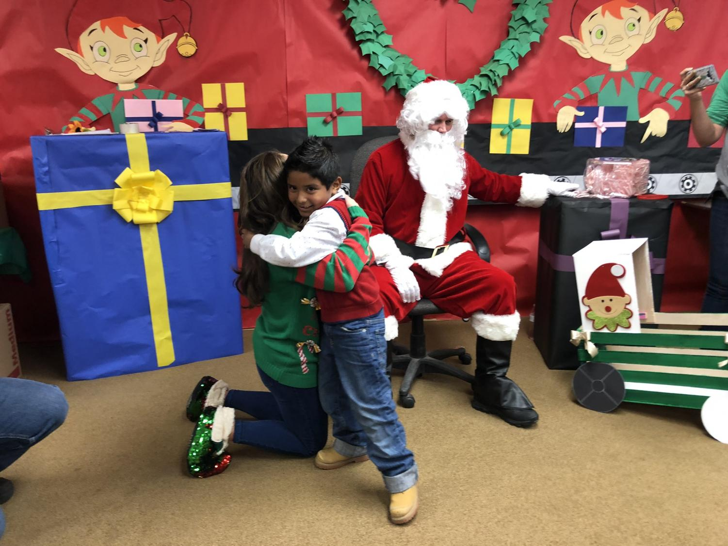 Students receive their gifts and meet Santa during last year's Holiday Blessings project.