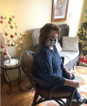 The author's grandmother in a chair in a house while wearing a mask. Not all individuals are able to work from home, which could put them and their families at risk of COVID-19. This danger will last longer if essential workers are not prioritized as one of the first groups to get the vaccine.