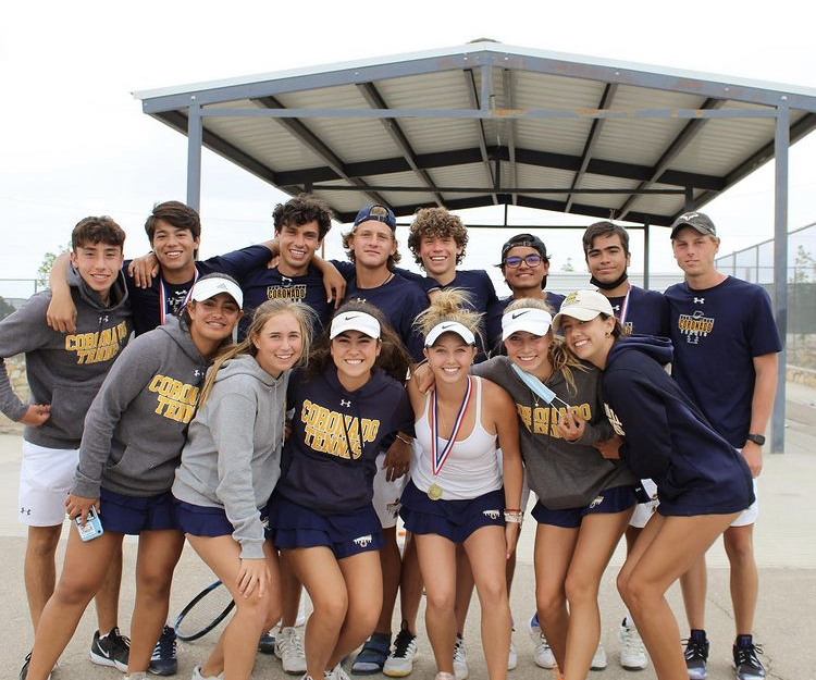 Members of the tennis team celebrate after finishing their district matches.